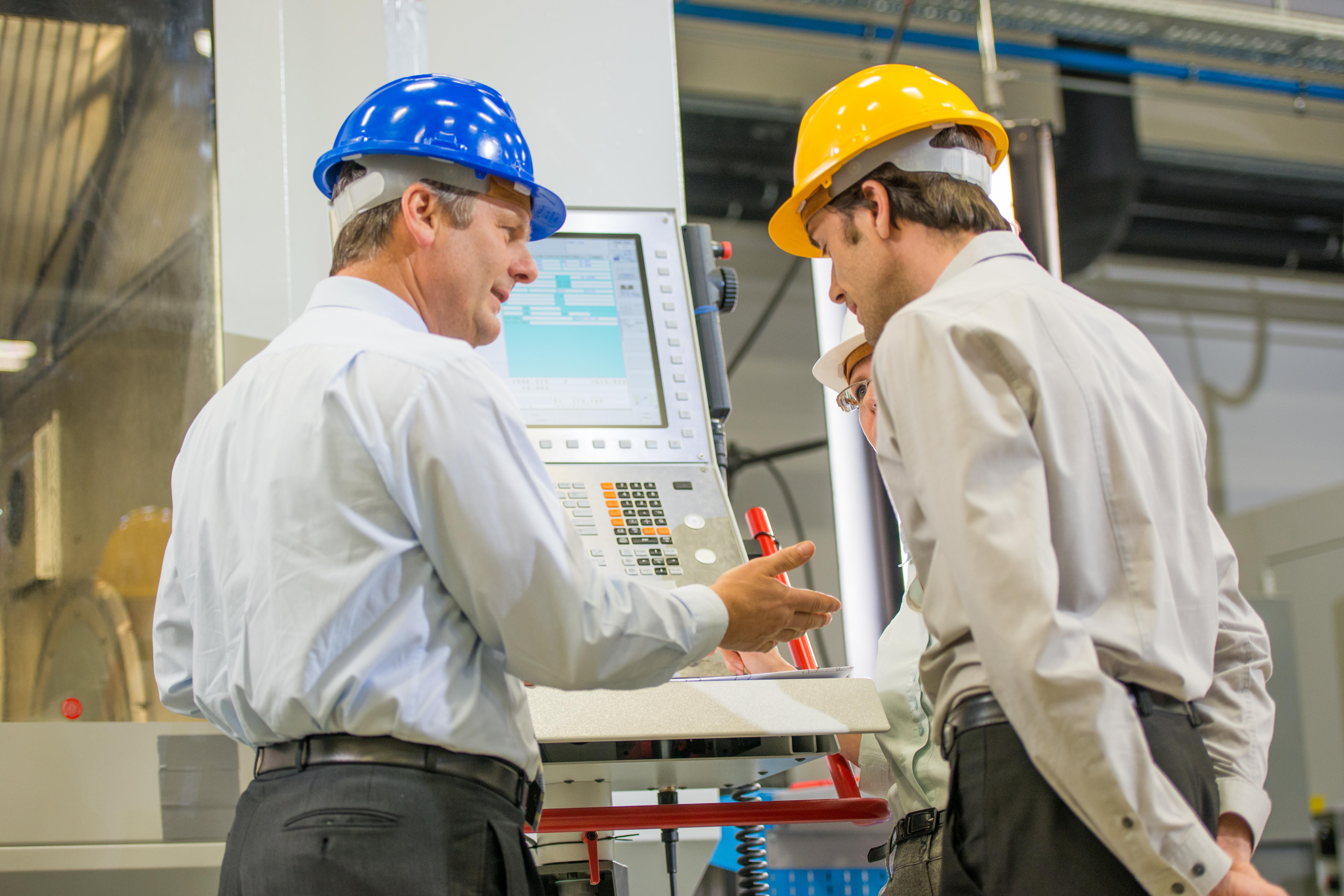Engineers Programming A CNC Machine